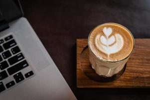 café con leche en un vaso sobre un escritorio de madera