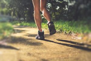 Person wearing running shoes on nature green background photo