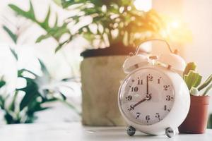 Selective focus of alarm clock showing 8 o'clock with nature bokeh background