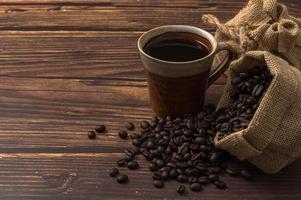 Coffee mug and coffee beans on the table photo