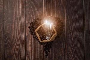 Coffee beans in heart shape, light bulbs emit energy photo