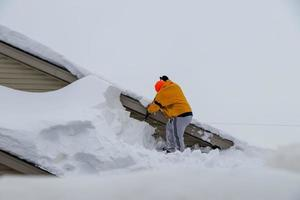 USA 2019- A man cleans snow from the roof of a house after blizzard