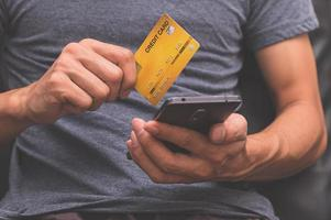 Man using a credit card and smartphone