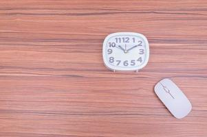 Mouse and a clock on wooden background photo