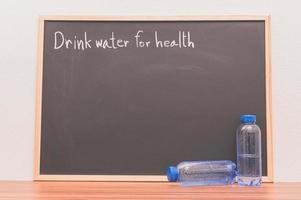 Botellas de agua potable contra la pizarra foto