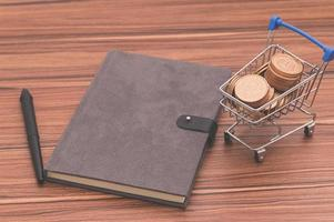 Notebook on the desk with coins in a tiny cart