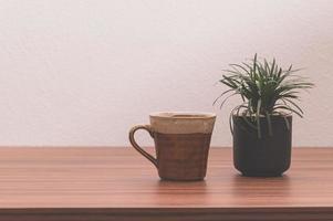 taza de café y planta en maceta sobre la mesa foto