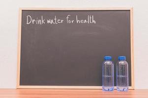 Bottles of drinking water against chalkboard photo