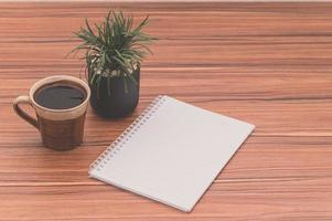 Notebook on the desk with coffee and a plant