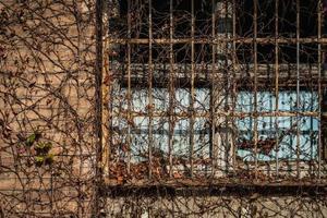 Ventana enrejada envejecida de una antigua fábrica foto