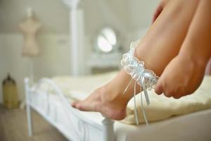 Bride putting on bridal garter indoors photo