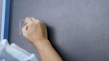 close-up de uma mão segurando um giz e escrevendo de volta para a escola na lousa video