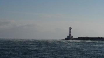 um farol, névoa sobre a água e gaivotas