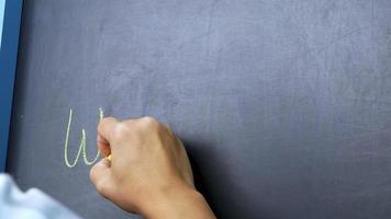 close-up de uma mão segurando um giz e escrevendo boas-vindas na lousa video