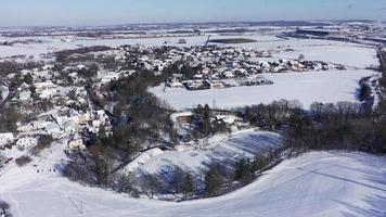 Aerial View of A Frozen Snowy Lake and Village on A Sunny Winter Day in 4 K