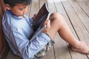 Niño sentado contra la puerta de madera leyendo un libro sobre un piso de madera foto