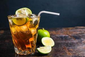 Iced tea and sliced limes on a wood tray on a wooden table