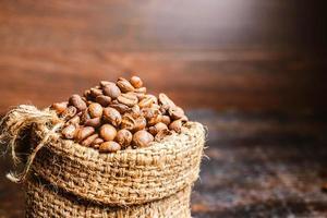 Granos de café en una bolsa de arpillera sobre una mesa de madera oscura. foto