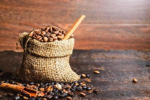 Granos de café y palitos de canela en una bolsa de arpillera sobre una mesa de madera oscura.