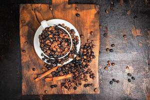 Granos de café en una taza blanca con platillo y ramitas de canela sobre una tabla para cortar madera sobre una mesa de madera oscura.