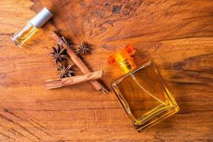 Bottles of perfume, cinnamon sticks, and anise seeds on a wood table
