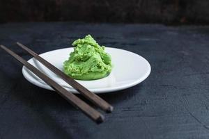 Wasabi on white plate with pair of chopsticks on black table background