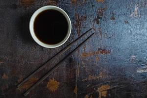 Cup of soy sauce with a pair of chopsticks on a dark wood background