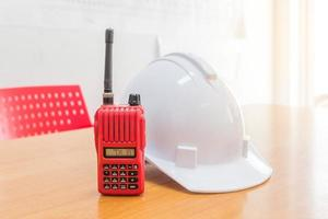 Red walkie-talkie radio and a white safety helmet