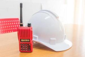 radio walkie-talkie rojo y un casco de seguridad blanco