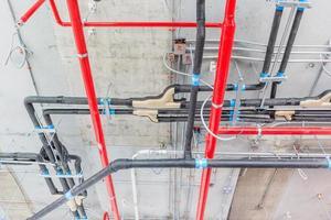 Tubos de ventilación en material aislante y rociadores contra incendios en tubo rojo foto