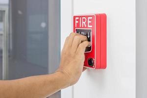 La mano del hombre tirando del interruptor de alarma contra incendios foto