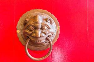 Martinete de metal de estilo chino tradicional en la puerta de madera roja foto