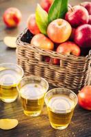jugo de manzana en vasos y manzanas en la canasta foto