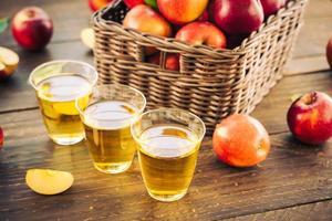jugo de manzana en vasos y manzanas en la canasta