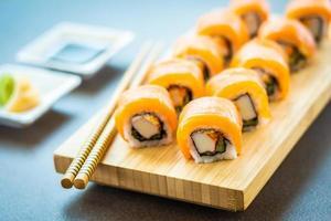 Rollos de sushi de salmón en placa de madera