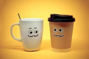 Smiley coffee cups on yellow background photo