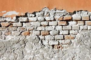 Partially damaged old brick wall