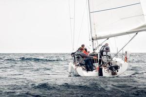 Equipo de vela de regata 2019: barco rompiendo un mar tempestuoso