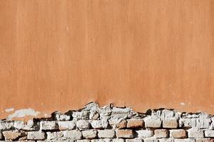 Yeso desgastado viejo en la pared de ladrillo foto