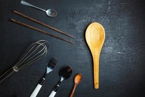 Kitchen utensils on black table background photo