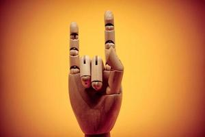 Rock on hand gesture on bright orange background photo