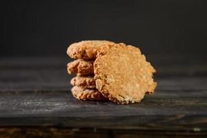 Pile of oat cookies on wooden table photo