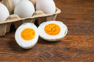 Sliced hard-boiled duck egg next to whole eggs in a carton on a wooden table photo