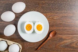 Halved hard-boiled duck egg on a white plate next to whole eggs on a wooden table photo