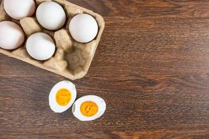 Halved hard-boiled duck egg next to whole eggs in a carton on a wooden table photo