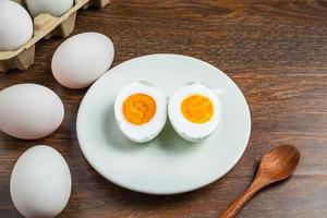 Sliced hard-boiled duck egg on a white plate next to whole eggs in a carton on a wooden table photo
