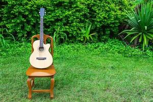Accoustic guitar on a wooden chair in a yard with shrubbery photo