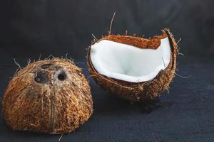 Coco cortado por la mitad sobre un fondo de tabla negro