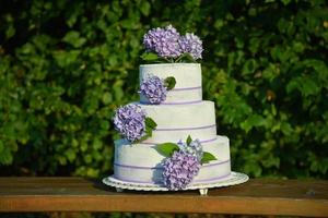 A photo of a wedding cake with violet colored flowers hydrangeas