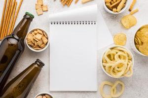 Cuaderno vacío con cerveza y bocadillos. foto